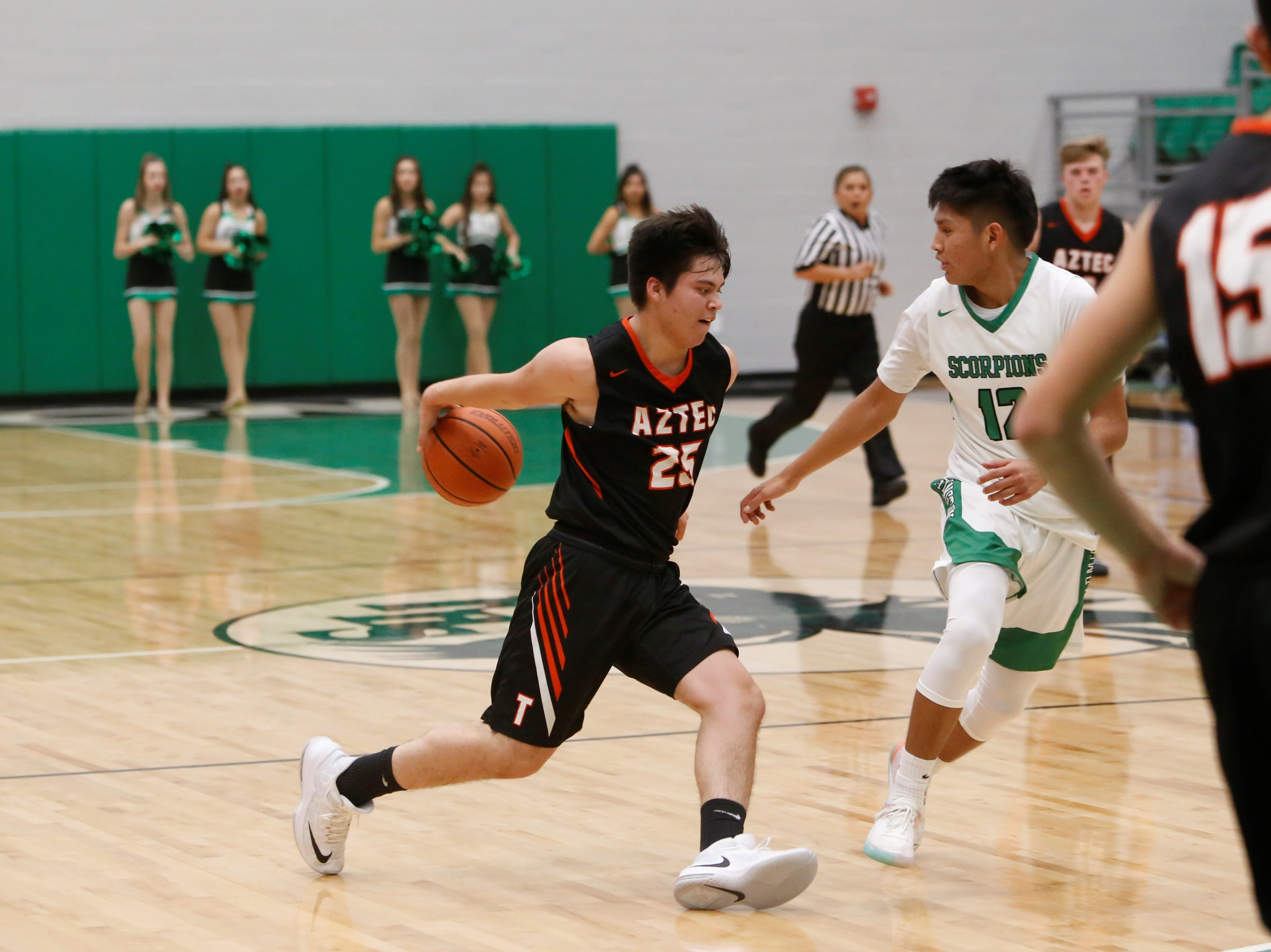 Aztec's Isaac Robeson dribbles the ball behind his back and darts to the left against Farmington's Jordan Beyale during Thursday's Marv Sanders Invitational quarterfinals at Scorpion Arena in Farmington.