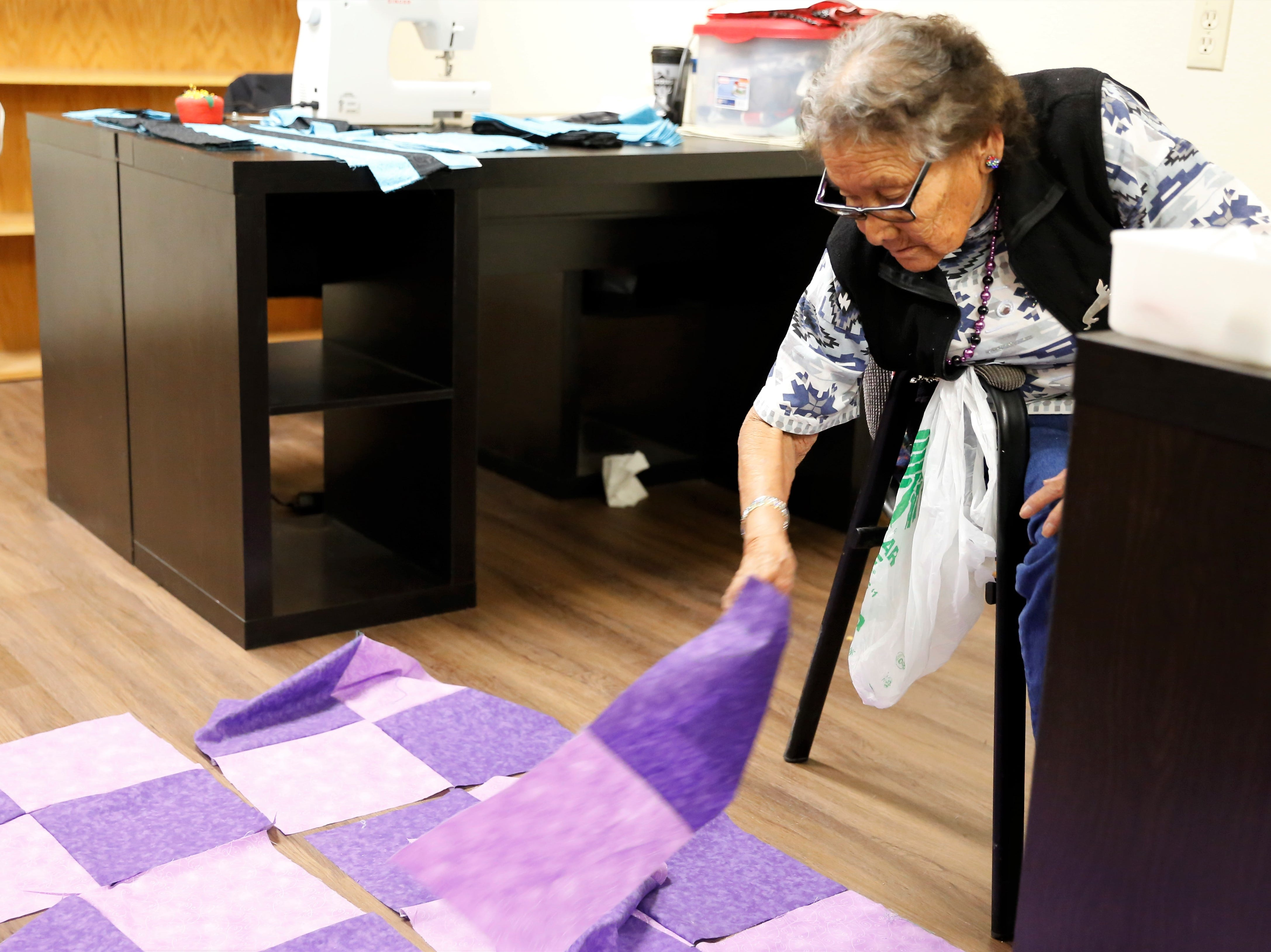 Abbie Allen organizes fabris squares for a quilt she was sewing on Wednesday at the Nenahnezad Chapter house.