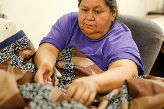 Martha Rey finishes work on a pinwheel quilt on Wednesday at the Nenahnezad Chapter house.