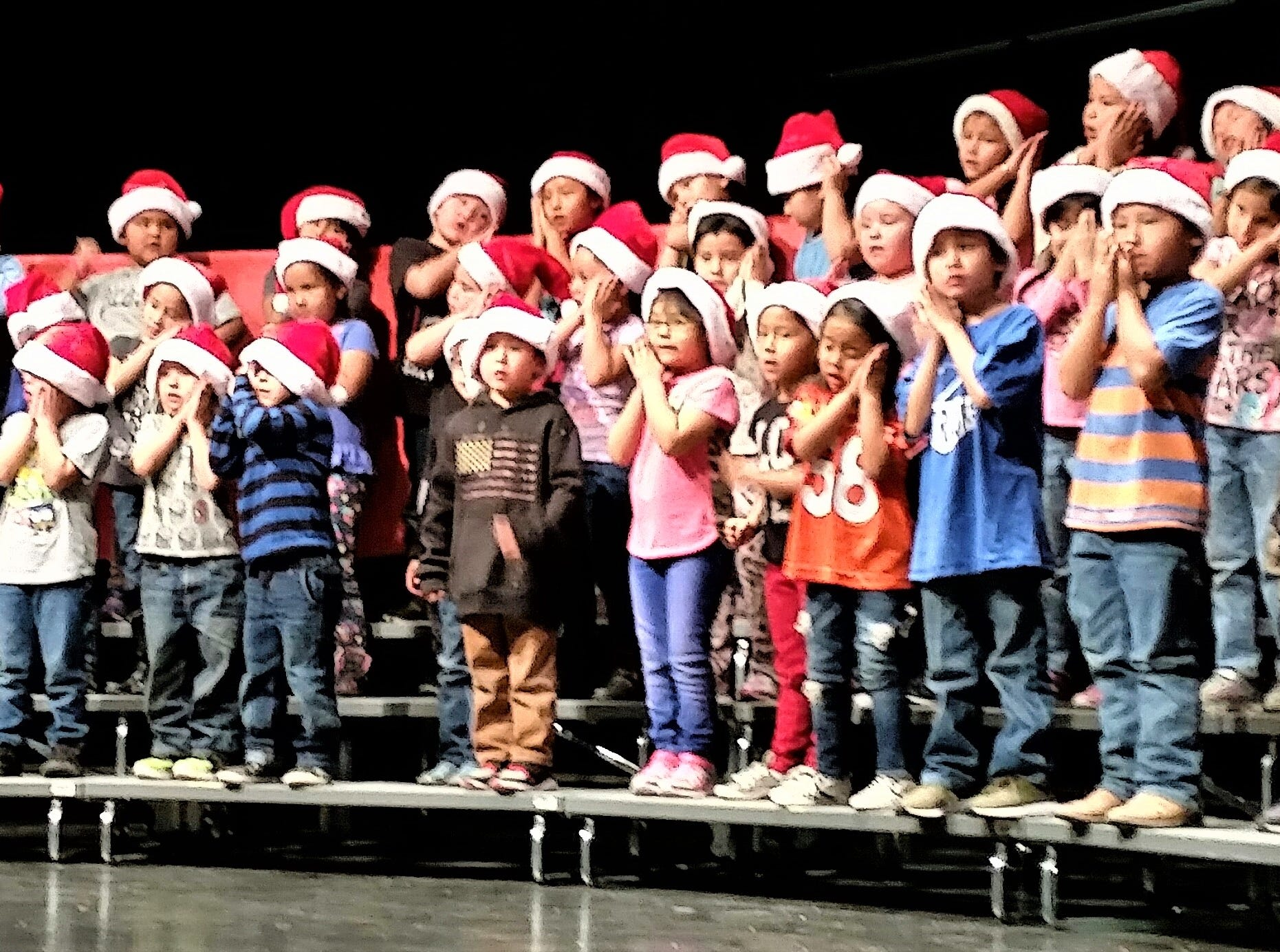 "Mescalero Apache Elementary School staged its annual Christmas program Thursday,  Dec. 6. Kindergarten teacher Dianna Jennings helps to direct the students in the song ""Coming Down The Chimney."""