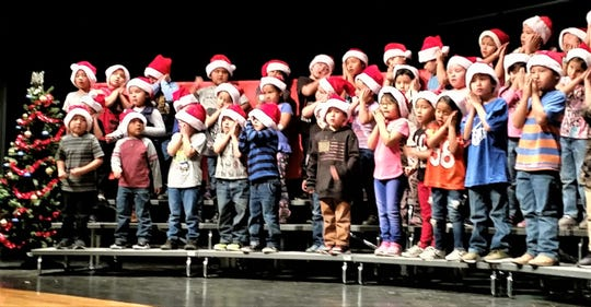 """Mescalero Apache Elementary School staged its annual Christmas program Thursday,  Dec. 6. Kindergarten teacher Dianna Jennings helps to direct the students in the song """"Coming Down The Chimney."""""""