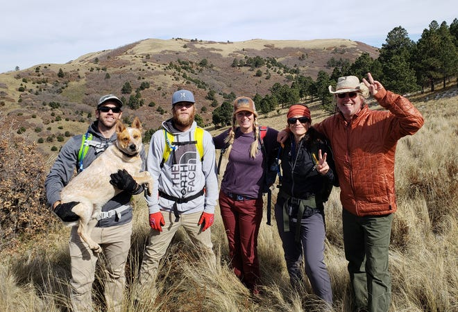 Pictured left to right, Matt who is holding Mojo, Layton, Anna, Heidi and Rich take a break while hiking on Tortolita Trail.
