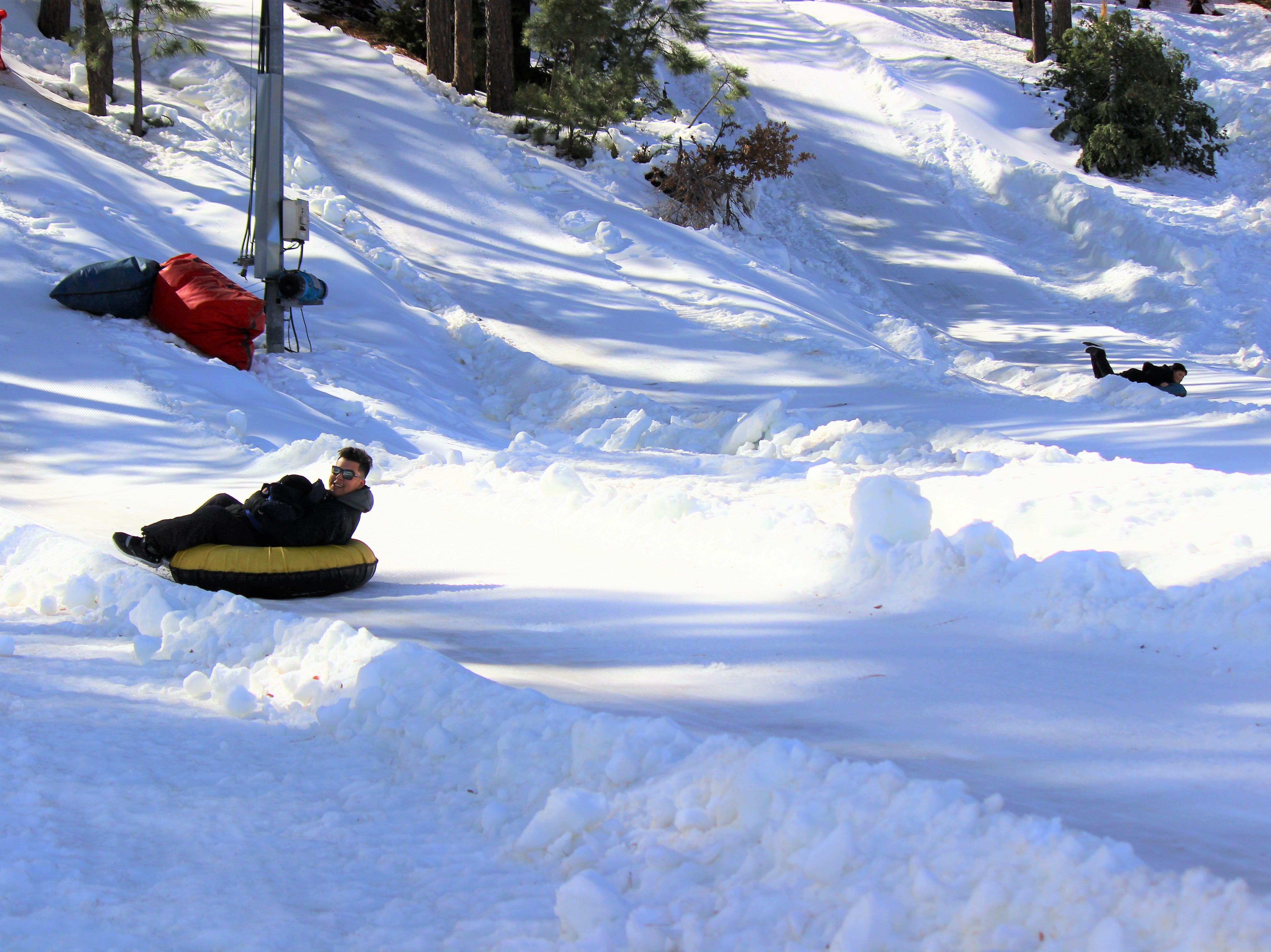 Even adults have fun snow tubing. The man is having a blast as he zooms down the hill on a snow tube.