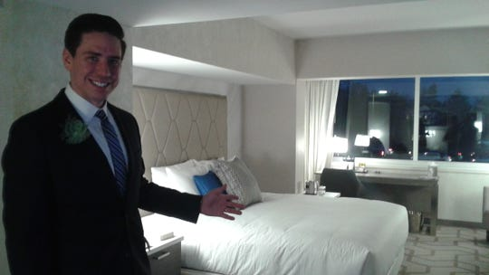 William Bornheimer, general manager, shows off a junior suite that faces Woodward Ave. The room's balcony was enclosed, which added a seating area with a desk. Bornheimer said many rooms on the Woodward Ave. side of the hotel have been booked for the Woodward Dream Cruise next year.