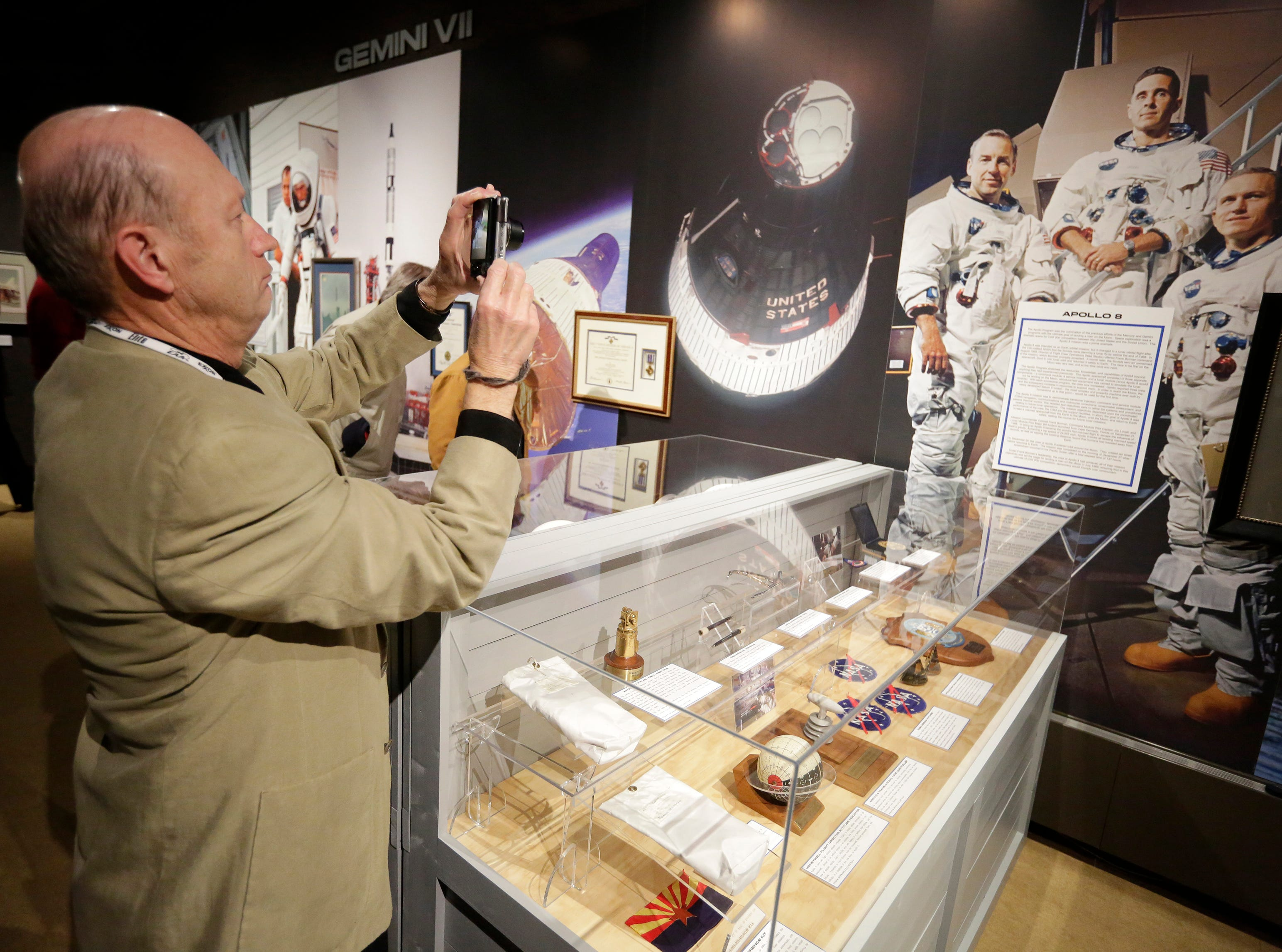 """Dave Weiman takes a photo of the astronauts at the exhibit opening.  The EAA Aviation Museum in Oshkosh, Wis. has opened """"The Borman Collection: An EAA Member's Space Odyssey,"""" an exhibit that features the personal archives and memorabilia of astronaut Frank Borman, who was on the leading edge of America's space program through the 1960s. The new exhibit was formally opened with a ribbon cutting by Borman on Friday, December 7, 2018.Joe Sienkiewicz/USA Today NETWORK-Wisconsin"""