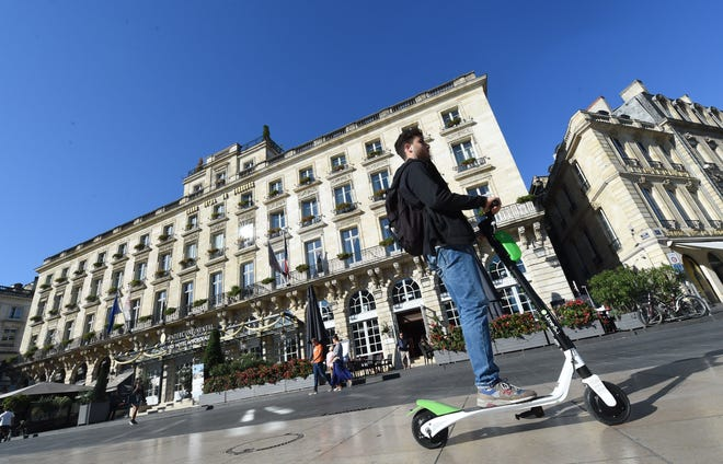 A man rides a Lime electric scooter on September 27, 2018, in the southwestern French city of Bordeaux.