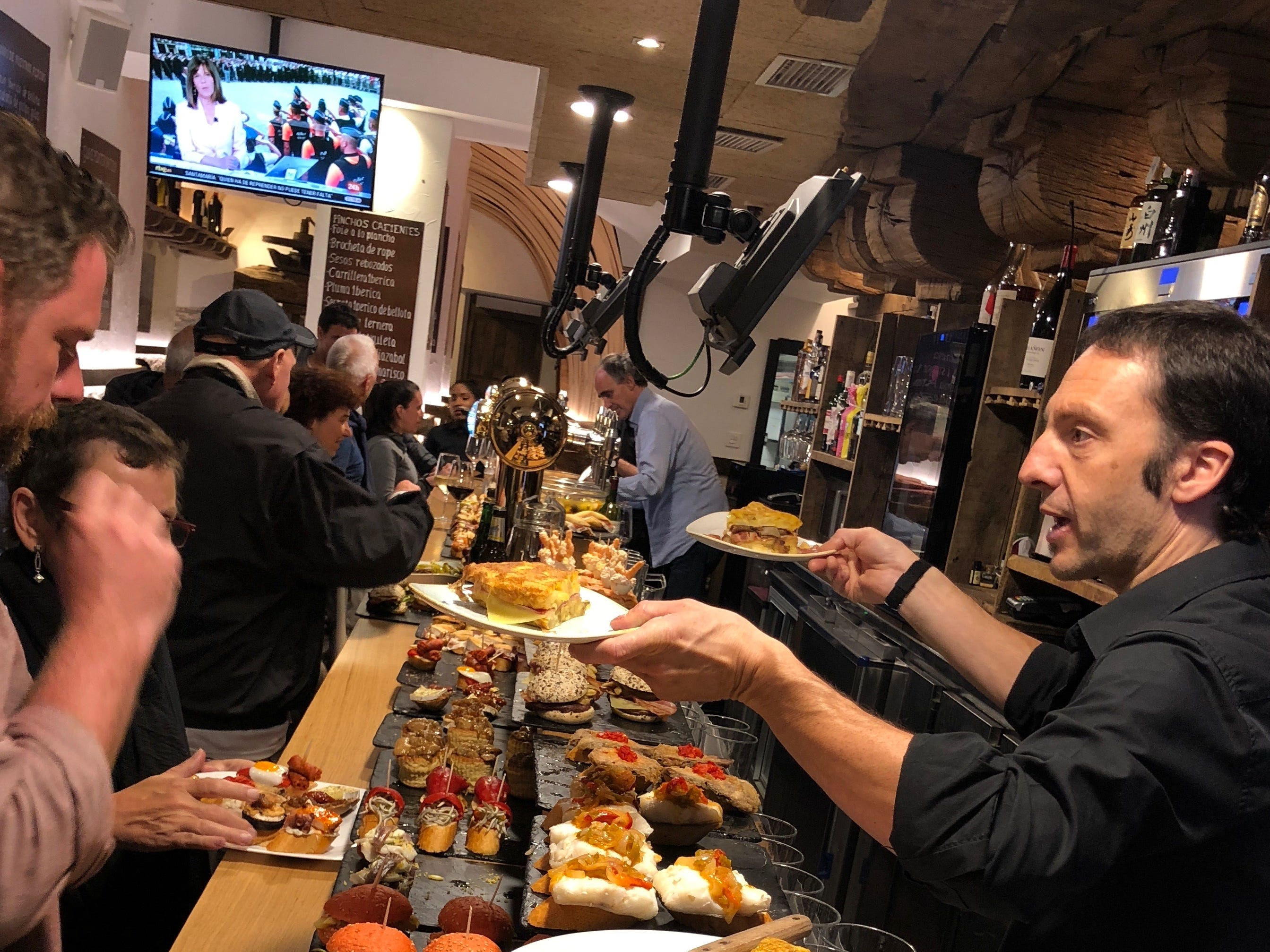 A bartender helps a patron order pintxos at Lete Taberna in San Sebastian, Spain. In the evening, tourists and residents alike go on pintxos crawls, grabbing bites at various taverns.
