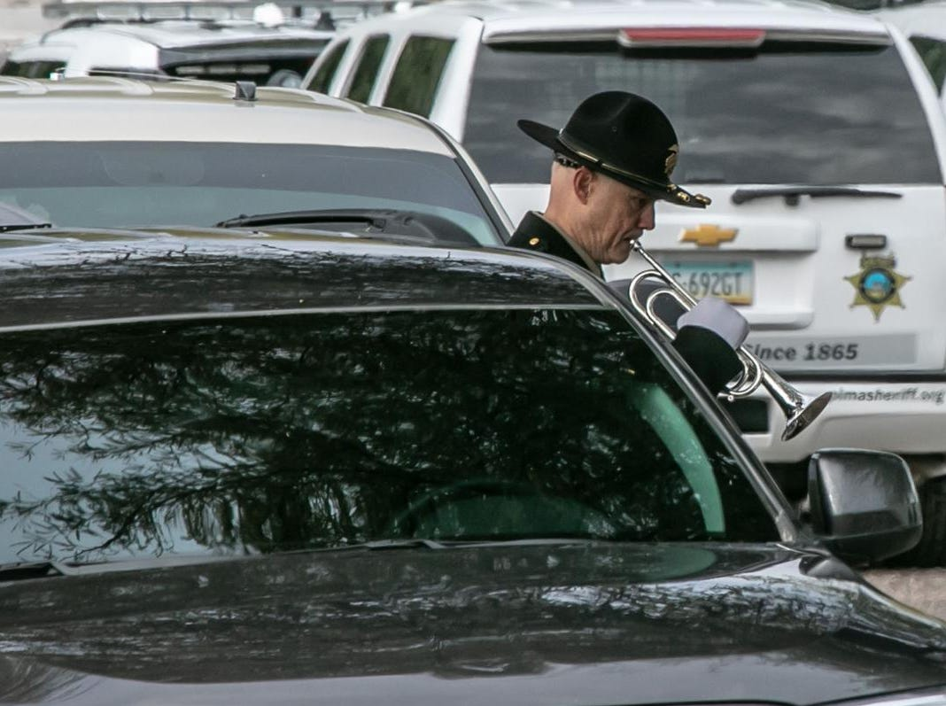 Pima County Sheriff's Deputy David Stivers takes a moment alone in the parking lot to warm up prior to playing taps at the memorial for fallen Deputy U.S. Marshal Chase White.