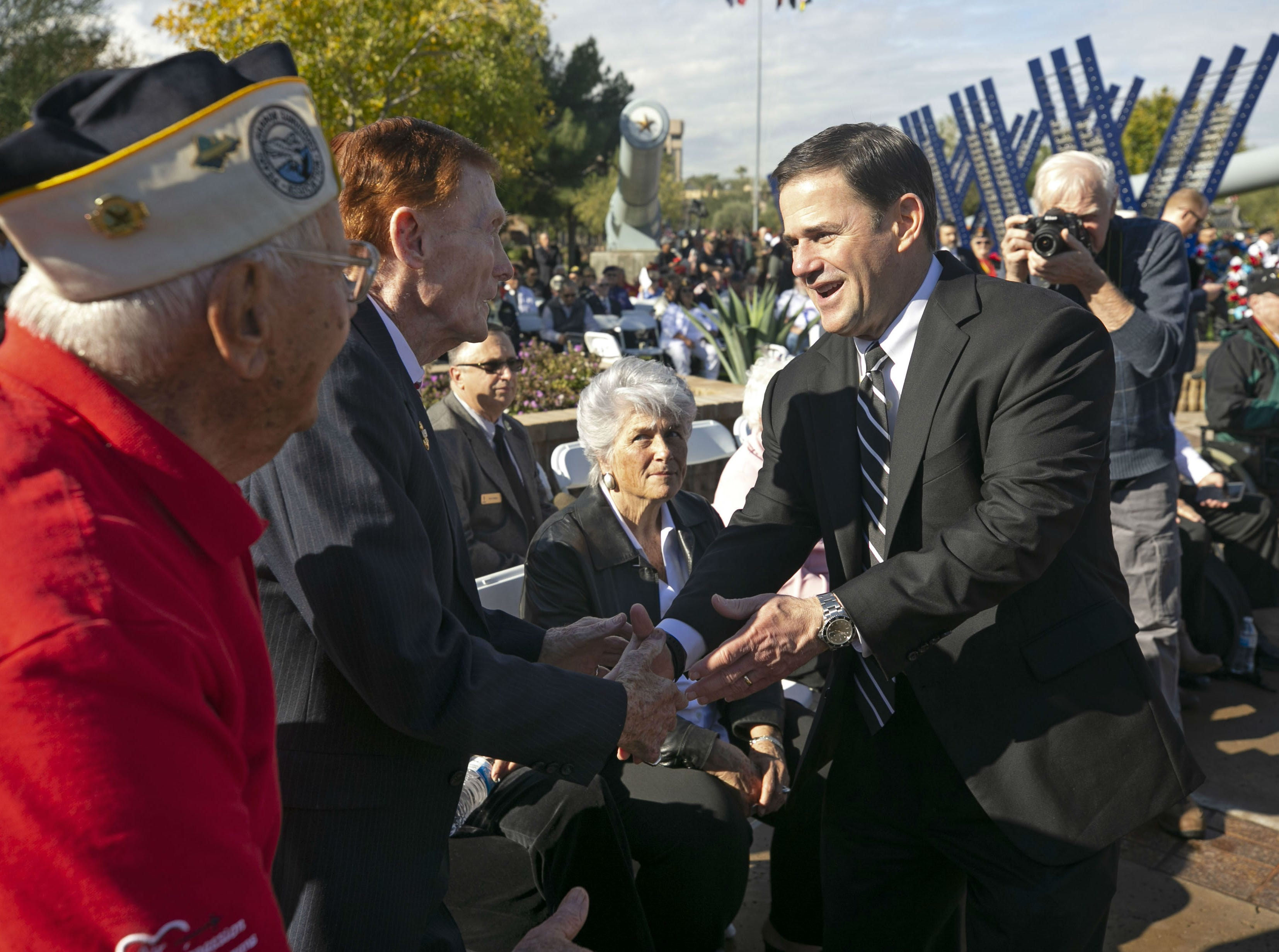 Gov. Doug Ducey shakes hands with Pearl Harbor survivors during a Pearl Harbor Remembrance Day event at Wesley Bolin Plaza in Phoenix on Dec. 7, 2018, the 77th anniversary of the attack on Pearl Harbor.