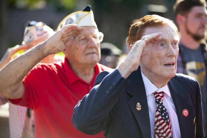 Pearl Harbor survivors Jack Holder (right) of Sun Lakes veteran of the U.S. Navy, and Edward Miklavcic (left), a Phoenix veteran of the then-U.S. Army Air Forces, salute during a Pearl Harbor Remembrance Day event at Wesley Bolin Plaza in Phoenix on Dec. 7, 2018, the 77th anniversary of the attack on Pearl Harbor.
