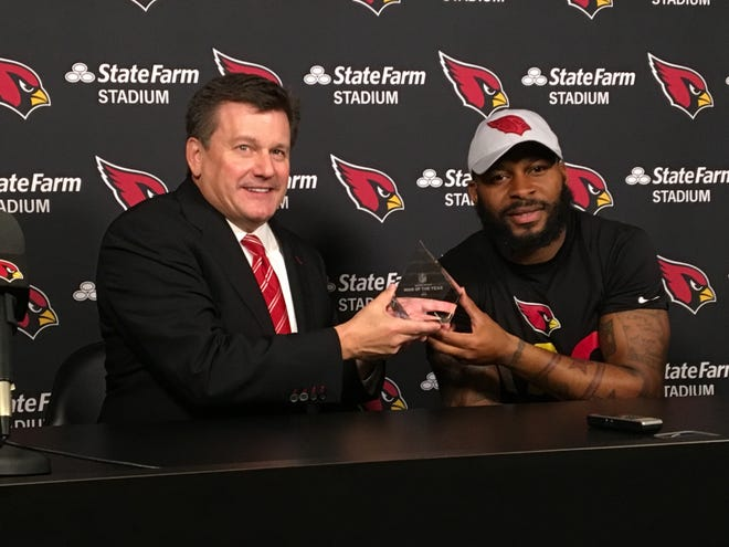 Cardinals President Michael Bidwill presents Antoine Bethea with the team's 2018 Walter Payton Man of the Year Award the team's practice facility on Thursday.