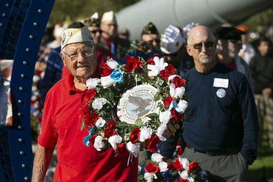 Pearl Harbor survivor Edward Miklavcic, a veteran of the then U.S. Army Air Forces, places a memorial wreath during a Pearl Harbor Remembrance Day event at Wesley Bolin Plaza in Phoenix on Dec. 7, 2018, the 77th anniversary of the attack on Pearl Harbor.