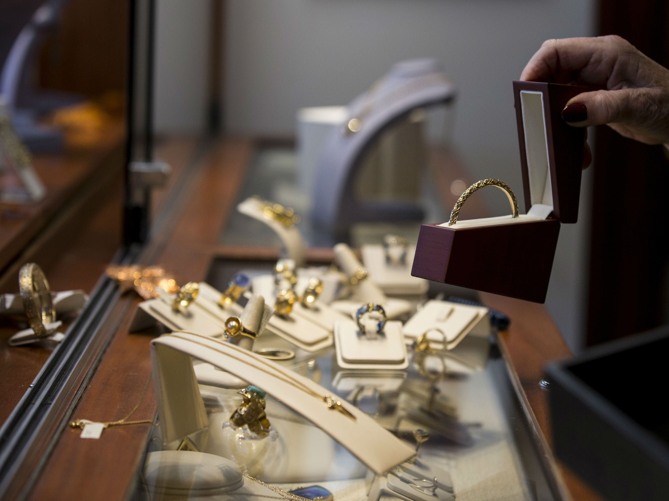 Vicky Boyce moves jewelry in a display on Nov. 19, 2018, at French Designer Jeweler in Scottsdale.