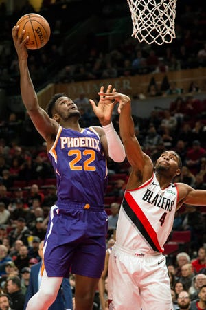 Suns center Deandre Ayton shoots over Trail Blazers forward Maurice Harkless during the first half of a game at the Moda Center.