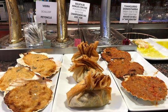 A selection of pintxos at Restaurante Bar Barandiaran in San Sebastian, Spain. Some of the tapas can be taken directly from the bar. Others like these, need to be heated up by the bartender.