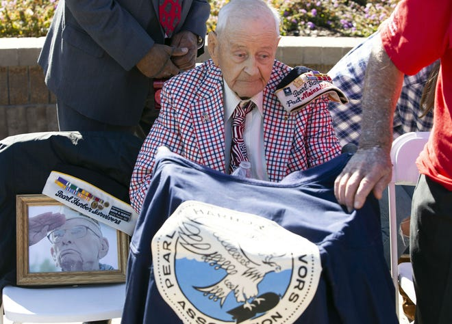 Pearl Harbor survivor Maurice Storck of Tucson, a veteran of the then U.S. Army Air Forces, holds his jacket during a Pearl Harbor Remembrance Day event at Wesley Bolin Plaza on Dec. 7, 2018. , He is sitting next to a photo of Pearl Harbor survivor Marvin Rewerts who passed away in November.