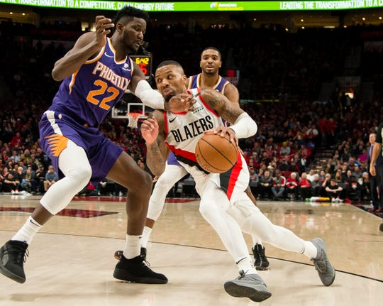 Trail Blazers guard Damian Lillard  drives to the basket against Suns center Deandre Ayton (22) during the second half of a game Thursday at the Moda Center.