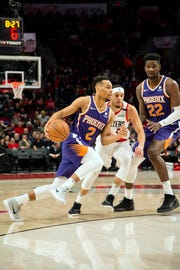 Suns rookie Elie Okobo drives to the basket against Trail Blazers guard Seth Curry during the first half of a game Thursday at the Moda Center.