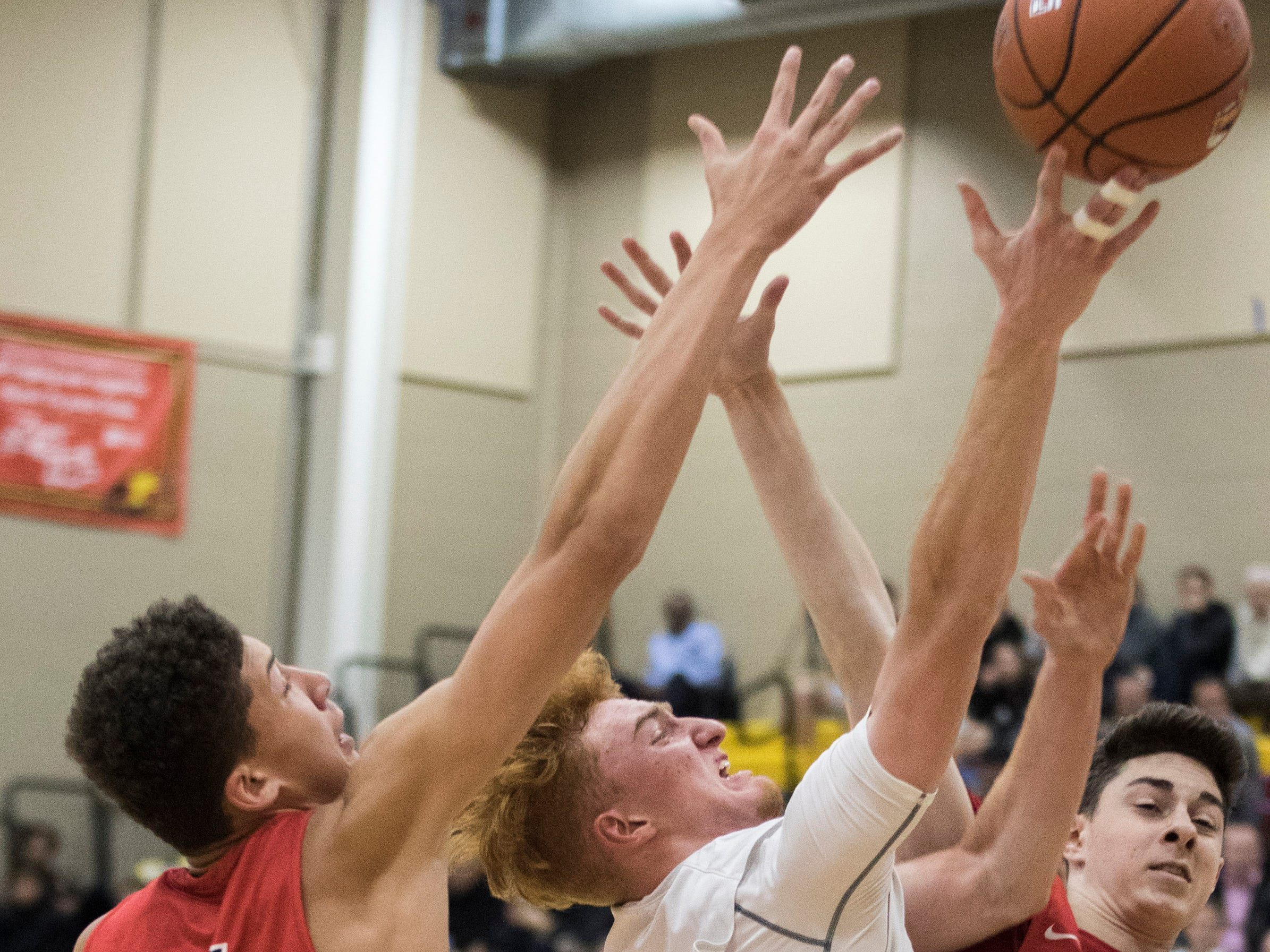 Pinnacle's Nico Mannion drives the lane and scores against San Joaquin Memorial's Braxton Meah (34) and Jaden Geron(1) during in the first half of their game in Scottsdale, Thurs, Dec. 6, 2018.