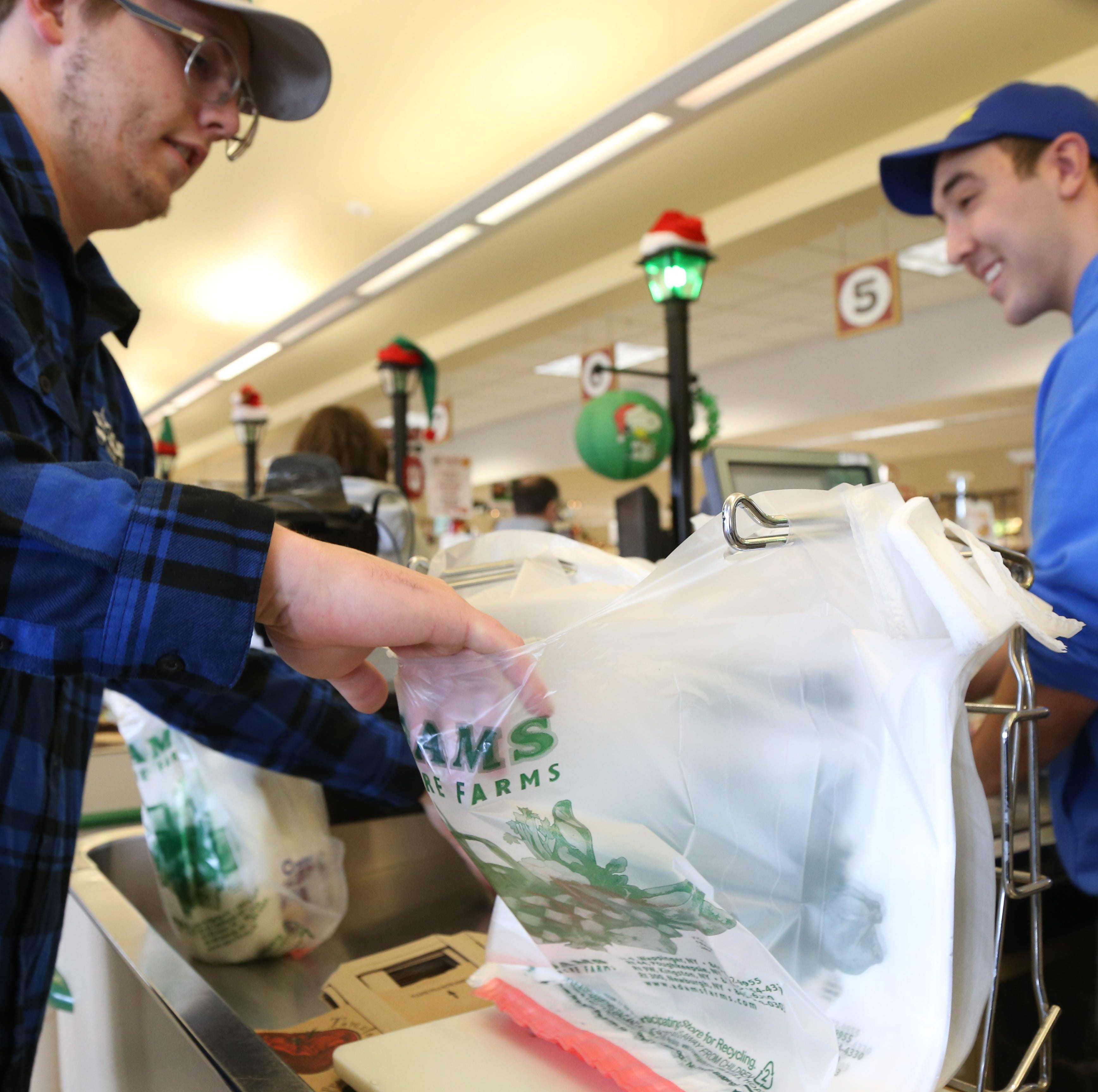 From left, front end supervisor Brian Owen and cashier Ricky Fusaro bag a customer's groceries at Adams Fairacre Farms in the Town of Wappinger on December 7, 2018.