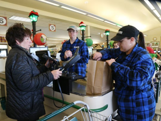 From left, front end supervisor Brian Owen and front end supervisor Megan Gonzalez bag Diane Hoffay's groceries at Adams Fairacre Farms in the Town of Wappinger on December 7, 2018.