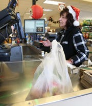 Cashier Donna Garrison rings up a customer who's groceries are in a plastic bag at Adams Fairacre Farms in the Town of Wappinger on December 7, 2018.