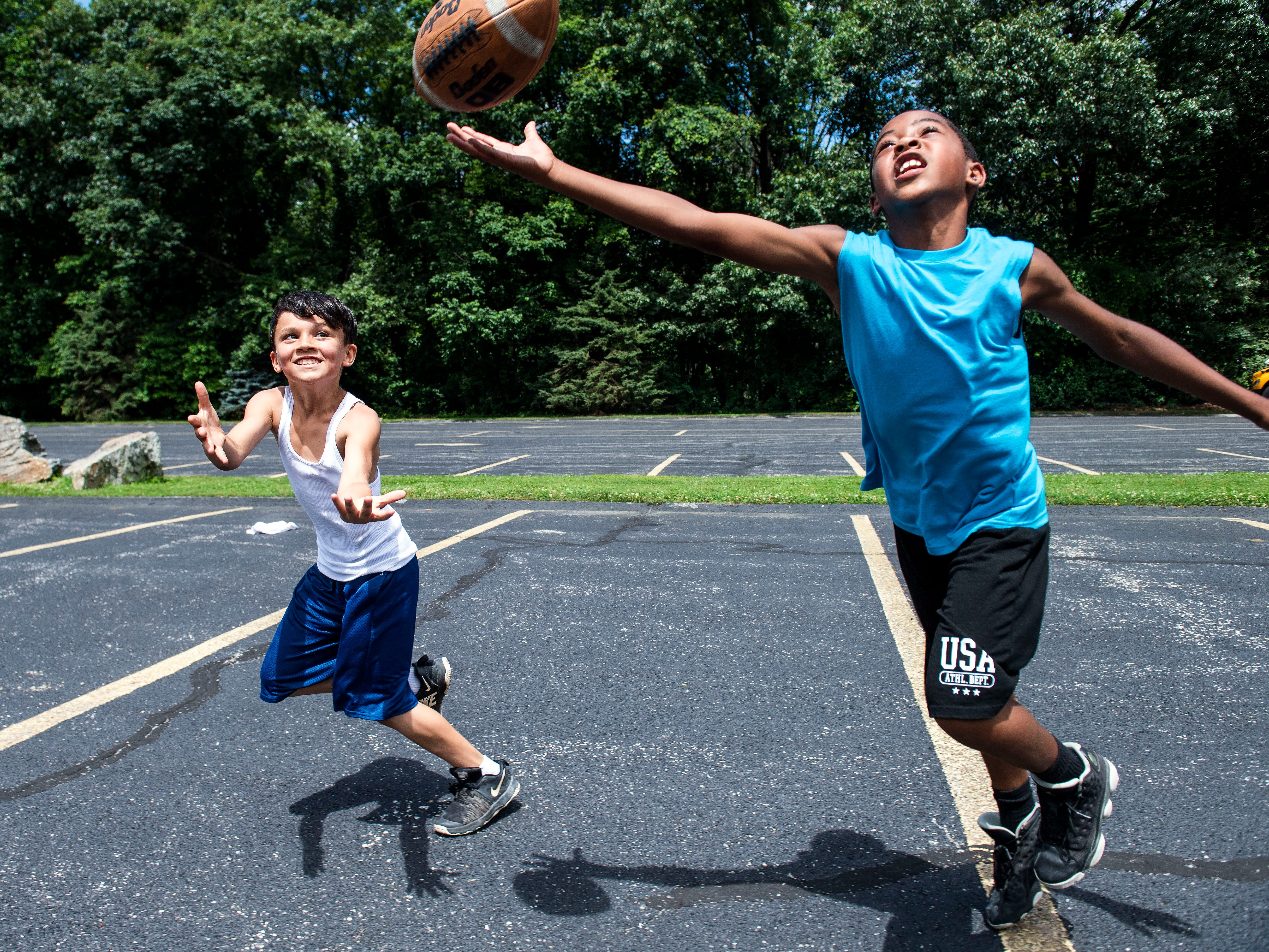 Conrad Beatty, 9, right, tips the ball while playing defense against Kyle Jackson, 10, on Thursday, June 28, 2018. Jordan Bowie, a 2017 Central York grad, spent the afternoon playing football with kids during his first year working with the St. Matthew Lutheran Church summer camp program at Rocky Ridge Park.