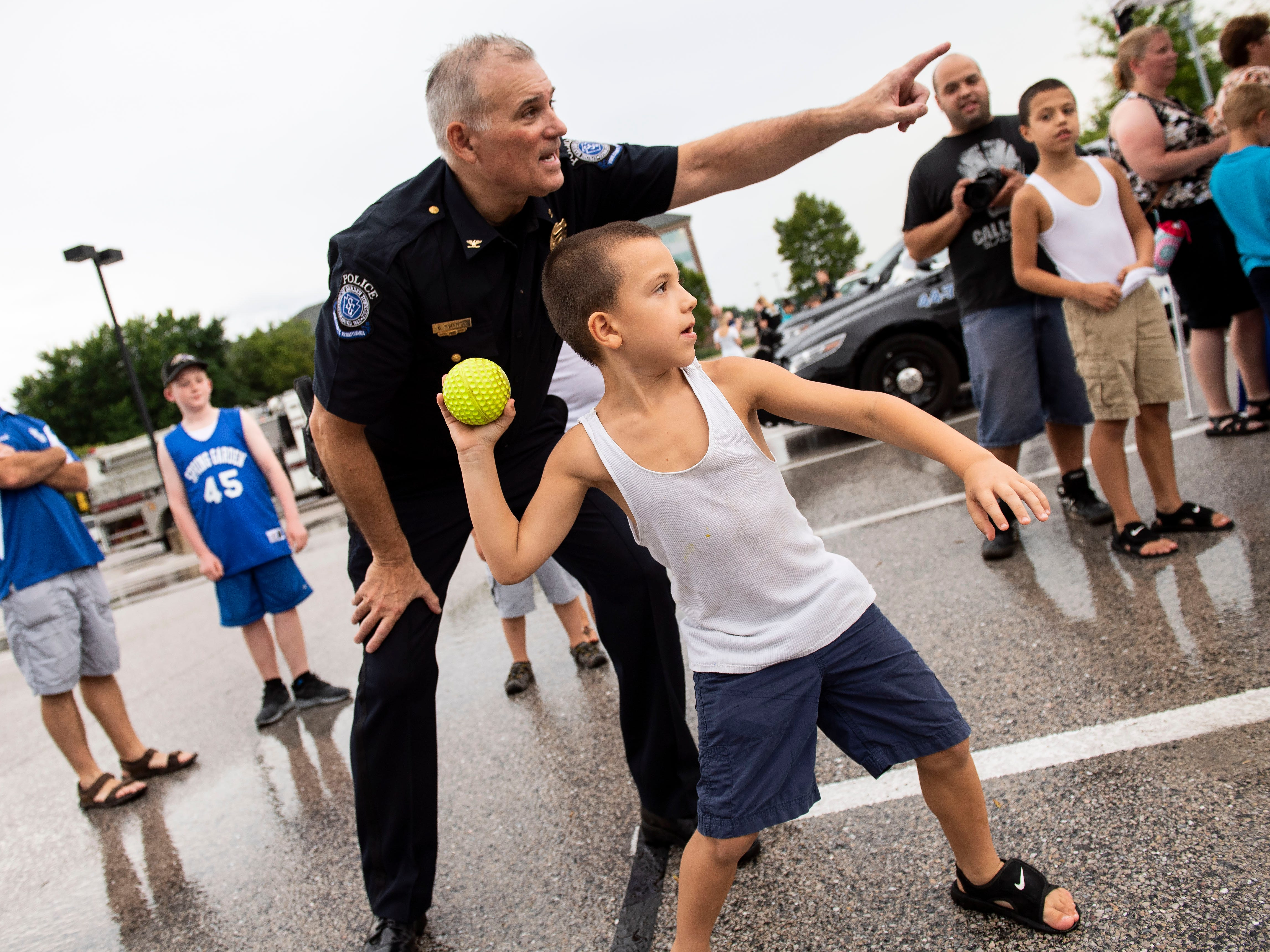 Spring Garden Township police chief George Swartz Jr. points toward the net as Orlando Cruz III, 6, of Spring Garden, winds up to throw a ball toward a police speed radar during National Night Out at York College on Tuesday, August 7, 2018. National Night Out is an annual community-building campaign that promotes police-community partnerships and neighborhood camaraderie, according to the National Association of Town Watch website.