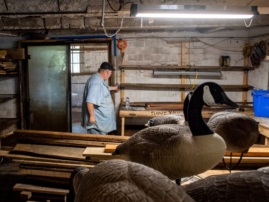 Bob Cooper hits the lights in his son's wood shop area of the Woodbine Saw Company building, showing the damage from the inside, Tuesday, September 4, 2018. Tools, lumber and inventory were all ruined in the Aug. 31 flooding.