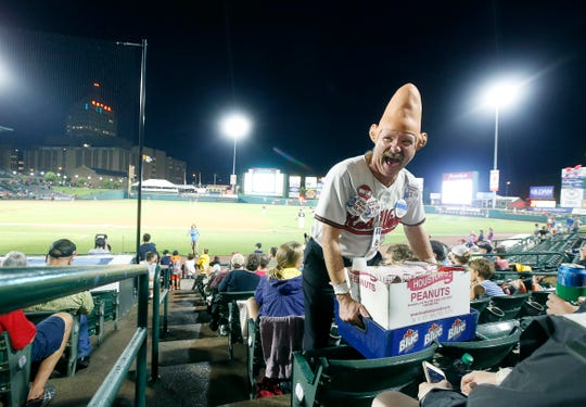 """Tom Girot, aka """"Conehead,'' has some laughs with customers after stating """"You can't be a vendor if you're gonna embarrass easily"""", while making his rounds at a Red Wings vs. Buffalo Bisons game at Frontier Field.  It was tough to follow Girot as he moved quickly from spectator to spectator, but after the rain stopped and the game started, everything was a bonus. So much energy, very professional and the character to keep up with clients knowing their preferences."""