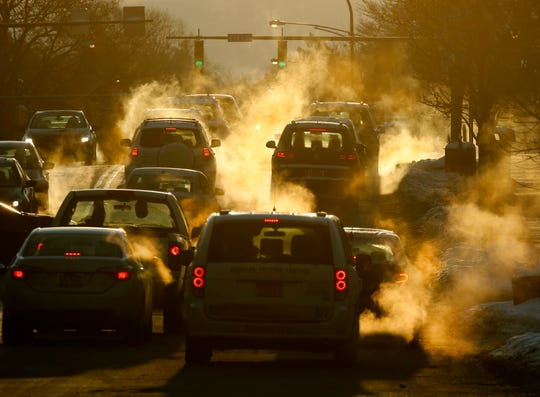 Drivers warm up their cars as the sun strikes Monroe Avenue on a 12-degree morning in downtown Rochester in 2018.