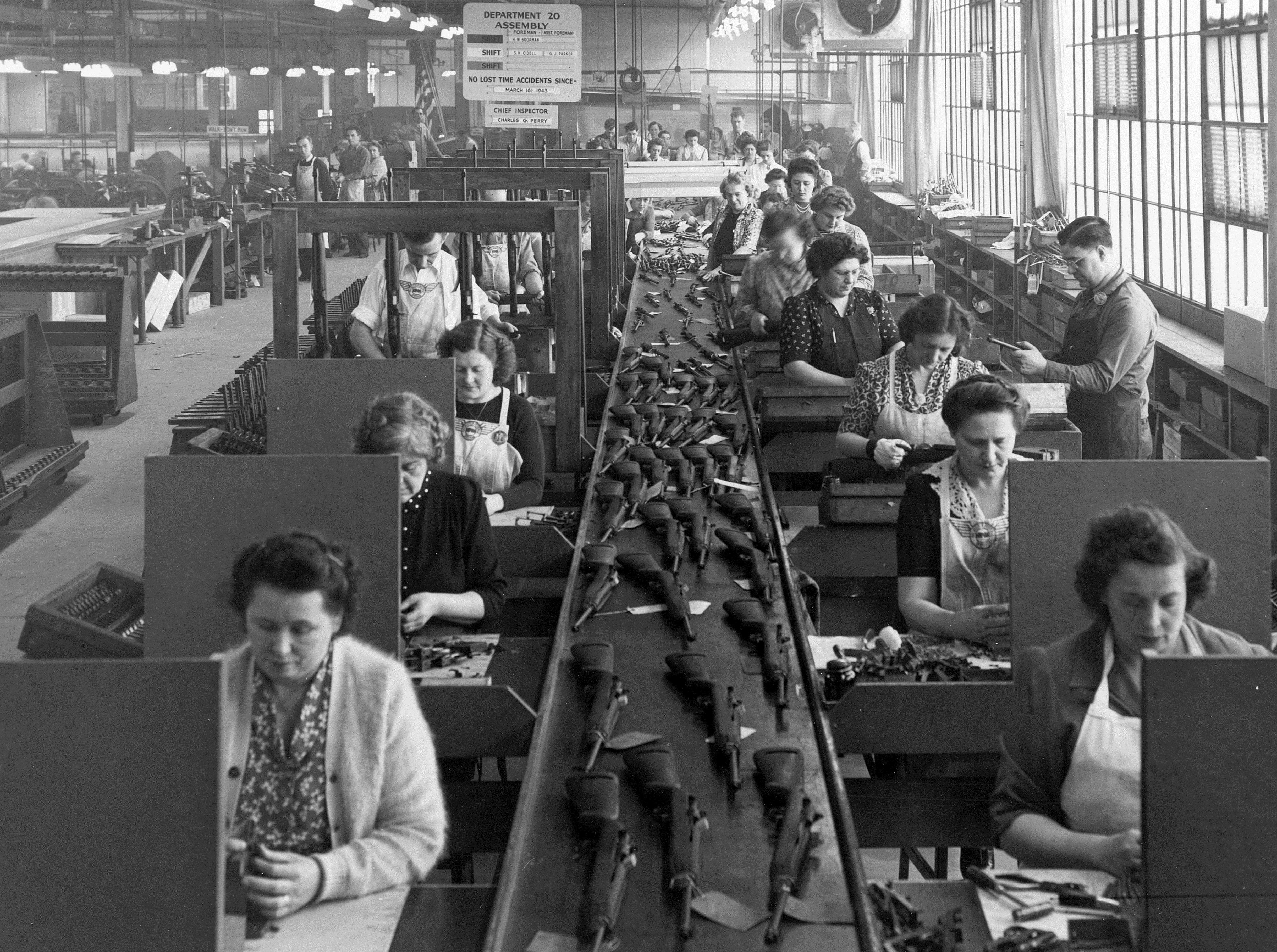 The final production line at National Postal Meter in Rochester during World War II. Carbines move along a conveyor belt with workers, nearly all women, on either side.