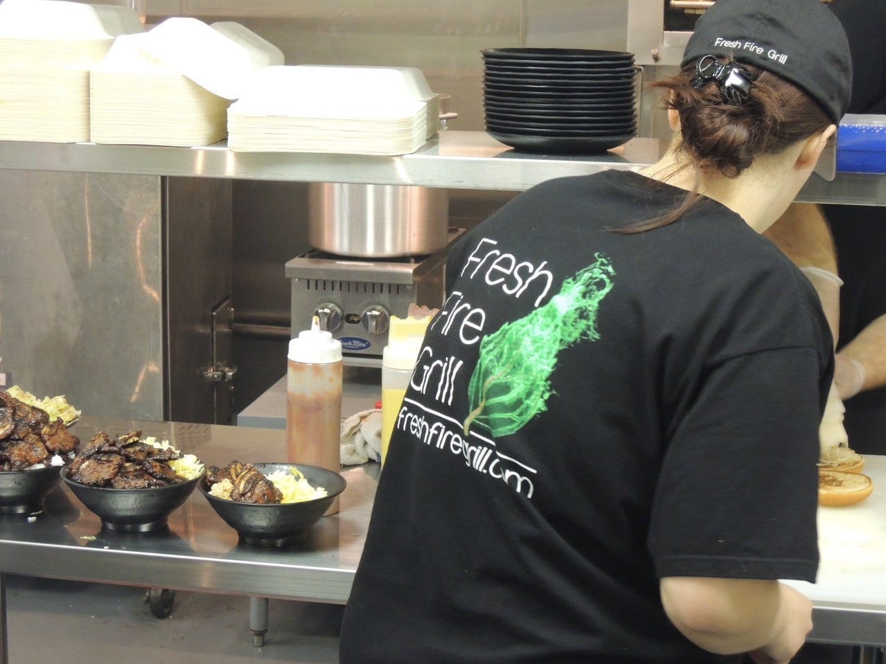 Laura Peyton prepares rice bowls and entree plates at Fresh Fire Grill on Lake Boulevard in Redding.