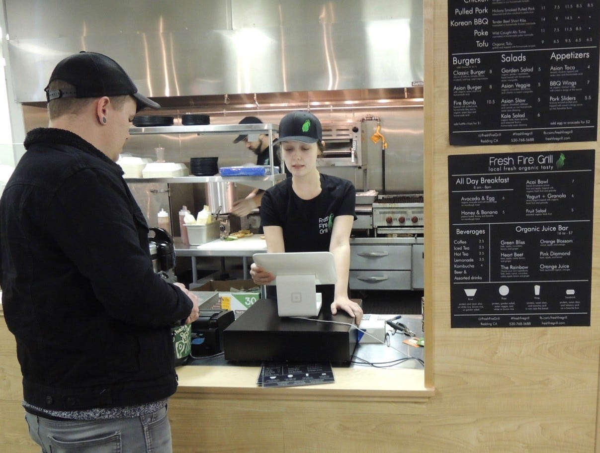 Dustin Schultz (left) places a dinner order with Destiny Wood at the new Fresh Fire Grill in north Redding.