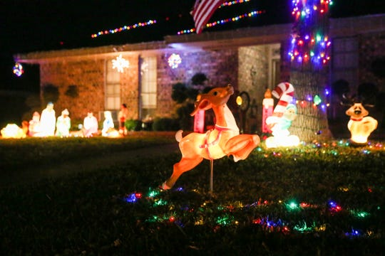 The family at 3026 Rock Brook Drive off College Hills Boulevard keep with tradition by using the older style light displays to illuminate their yard.