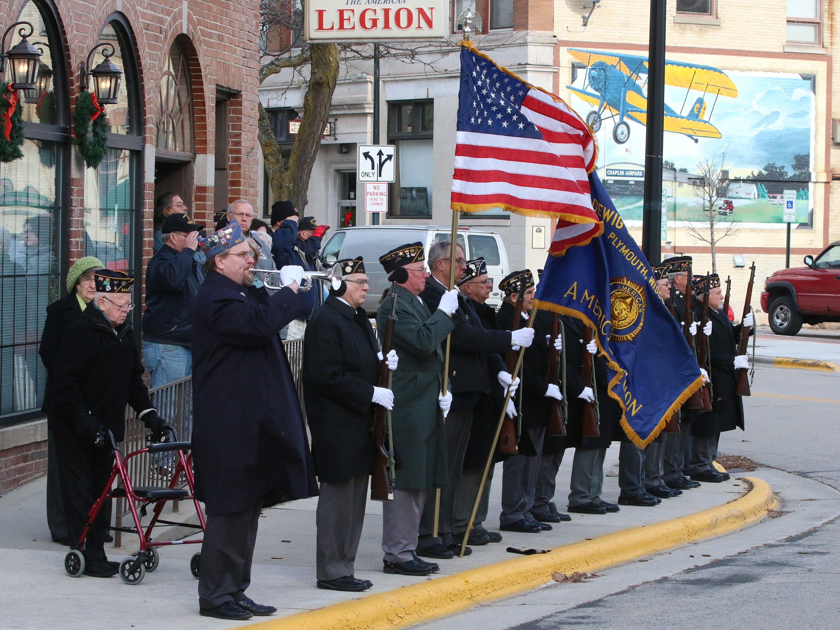 Members of American Legion Ladwig-Zinkgraf, Post 243, stand in formation during a ceremony honoring the soldiers who died at Pearl Harbor in 1941, while taps are performed by the Post's Michael Kalsbeek, Friday, December 7, 2018, in Plymouth, Wis.