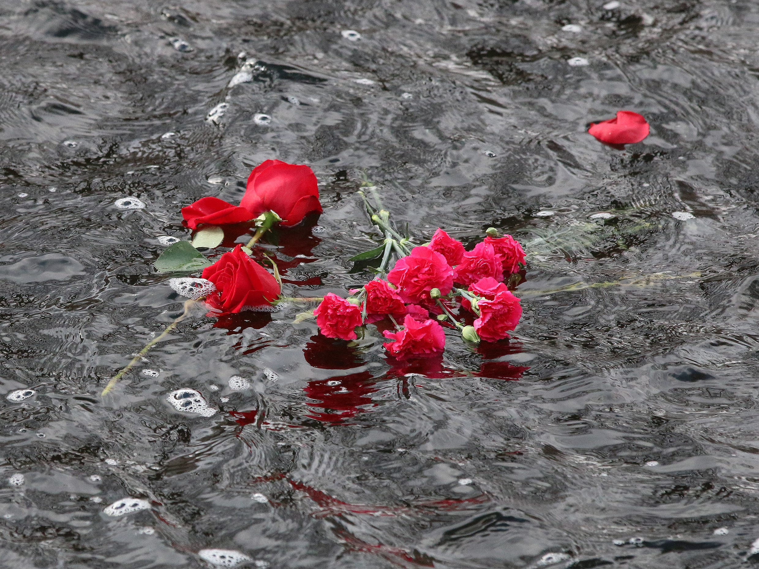Roses and carnations flow down the Mullett River in honor of those who died at Peal Harbor in 1941 during a ceremony, Friday, December 7, 2018, in Plymouth, Wis.