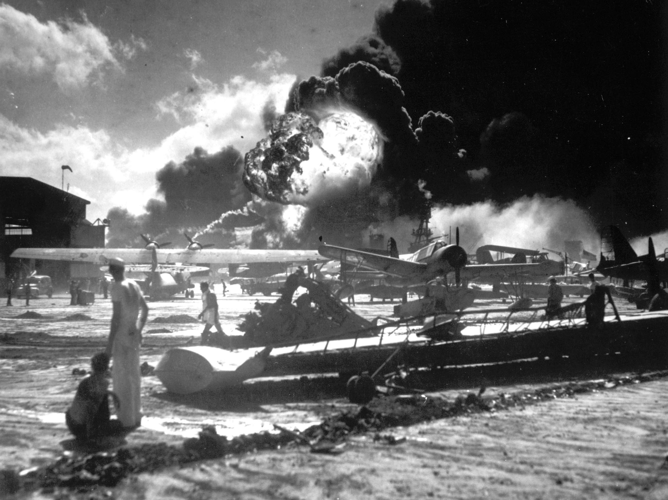 FILE - In this Dec. 7, 1941 photo provided by the U.S. Navy, sailors stand among wrecked airplanes at Ford Island Naval Air Station as they watch the explosion of the USS Shaw in the background, during the Japanese surprise attack on Pearl Harbor, Hawaii. (AP Photo/U.S. Navy)