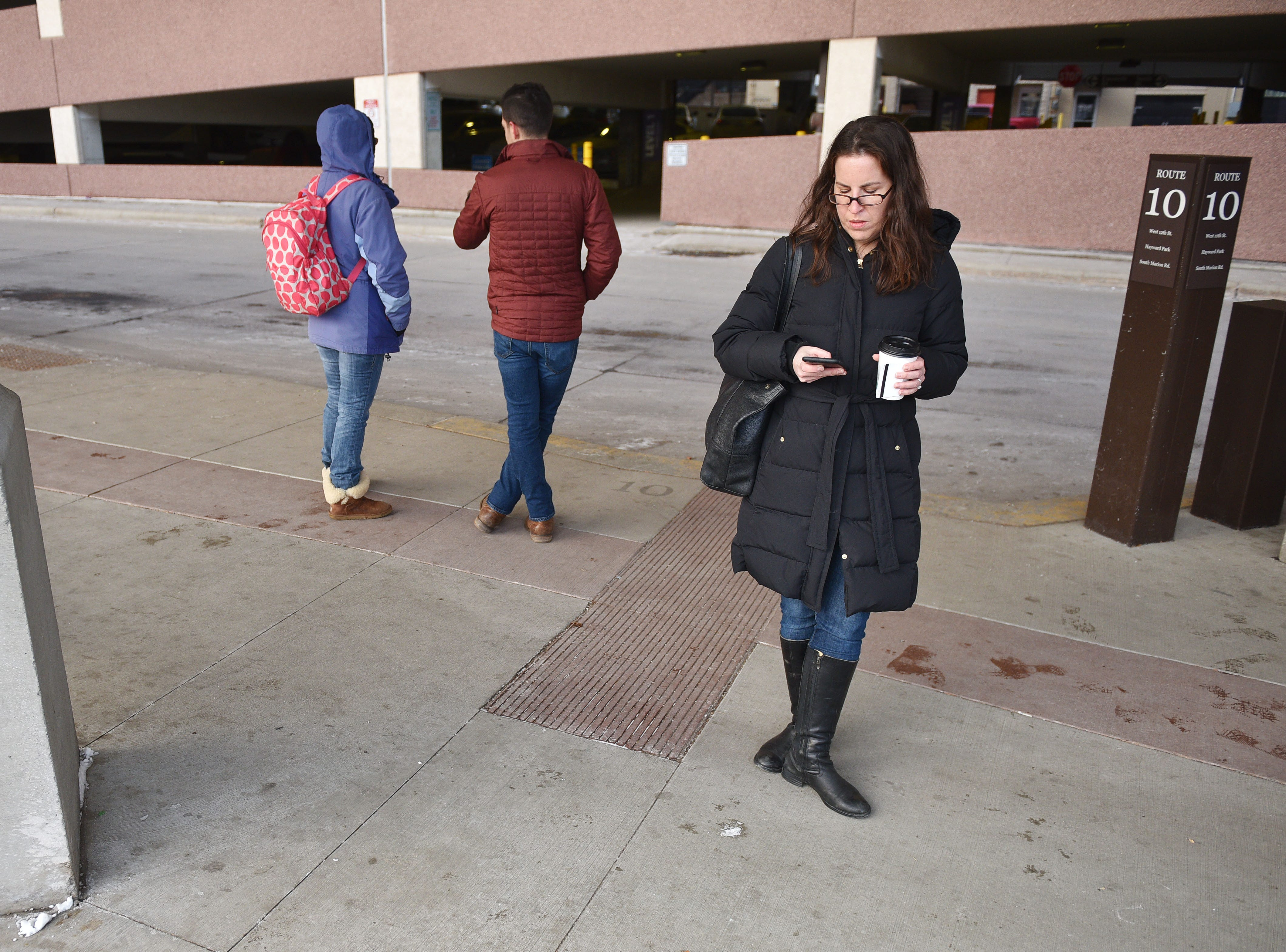 Harvard Bloomberg Institute Katie Appel Duda waits for her bus Friday, Dec. 7, in Sioux Falls. Public transit costs taxpayers millions each year. That's why a task force has been set up to study the issue with assistance from staff at the Harvard Bloomberg Institute. A part of the task force's work is engaging bus riders and the general public, so members were at the bus depot at 9 a.m. Friday to talk to riders and ride the buses.