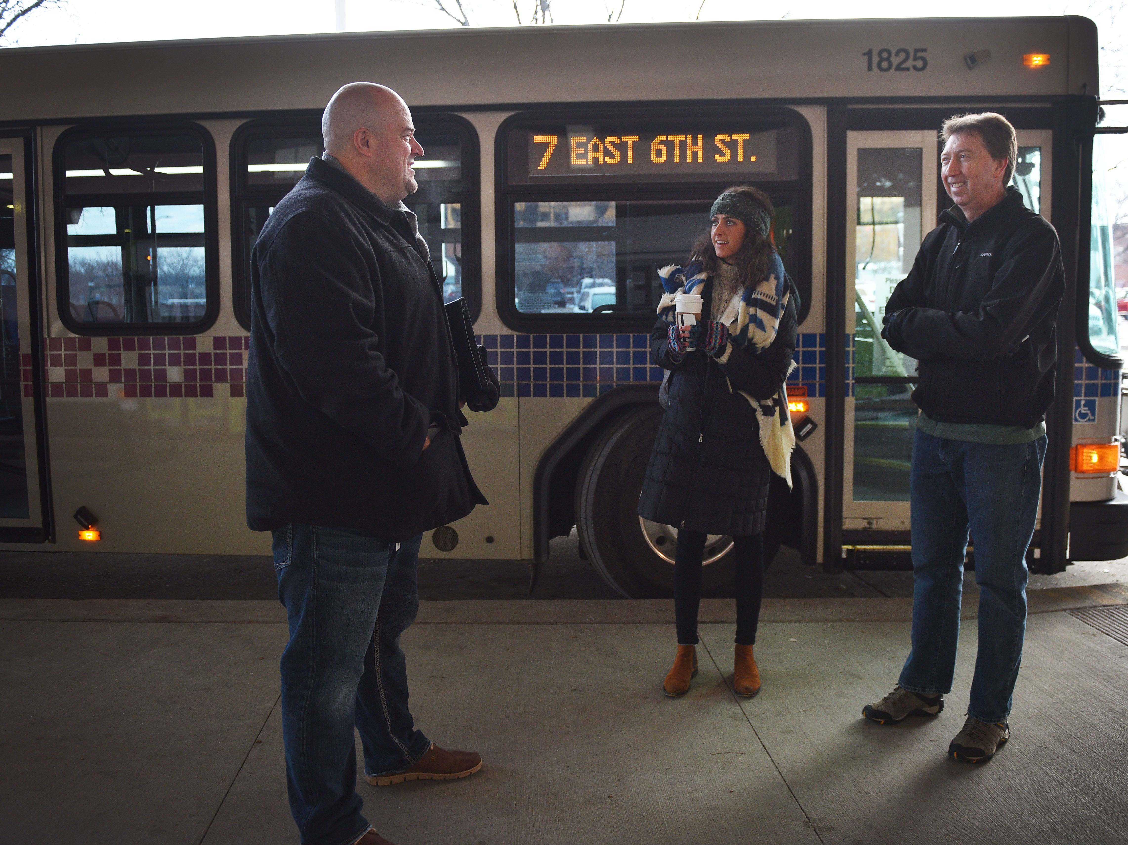 Innovation and technology director Jason Reisdorfer, from left, program Associate at Centre for Public Impact Paige Mcdermott and transportation planner Sam Trebilcock wait to get on a city bus Friday, Dec. 7, in Sioux Falls. Public transit costs taxpayers millions each year. That's why a task force has been set up to study the issue with assistance from staff at the Harvard Bloomberg Institute. A part of the task force's work is engaging bus riders and the general public, so members were at the bus depot at 9 a.m. Friday to talk to riders and ride the buses.