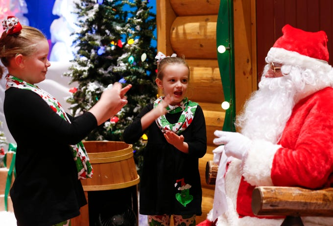 Sisters Maddie (left), 8, and Rylee Slye, 6, communicate their Christmas wishes in sign language to Santa Claus at Bass Pro Shops on Friday, December 7, 2018. More than 100 deaf and hard of hearing area students visited with the American Sign Language fluent Santa.