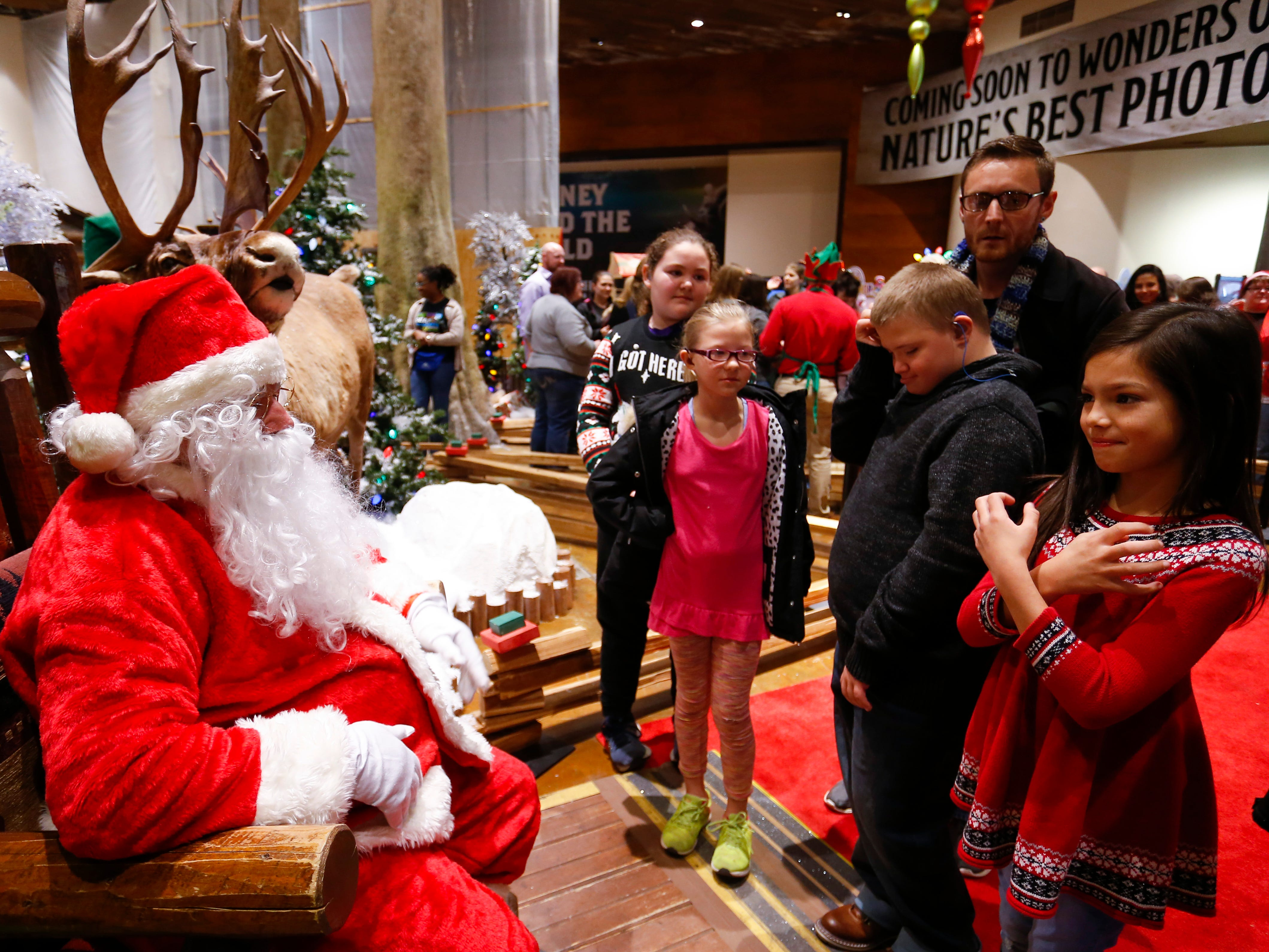 Nixa students (from right) Avery O'Brien, 8, Ayden Keating, 11, Ella McGarry, 10, and Samantha Surridge, 10, communicate their Christmas wishes in sign language to Santa Claus at Bass Pro Shops on Friday, December 7, 2018. More than 100 deaf and hard of hearing area students visited with the American Sign Language fluent Santa.