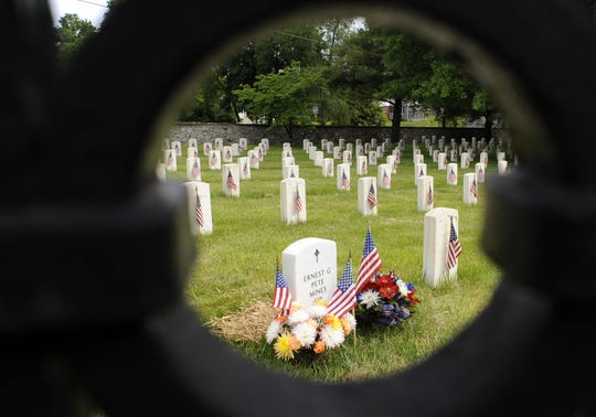 A circular design in an iron fence highlights graves with flags the weekend just before Memorial Day at the Staunton National Cemetery in 2009.