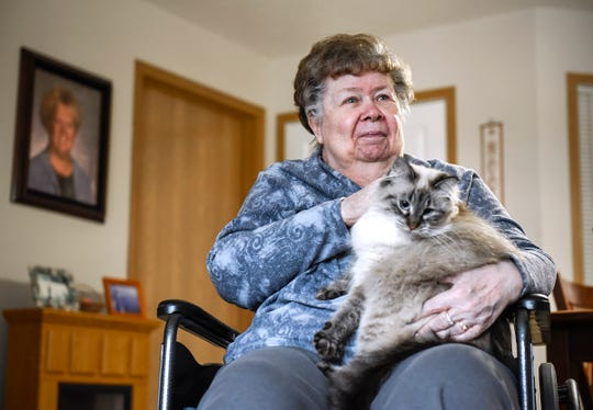 Barb Nelson holds her cat Wednesday, Dec. 5, at Ridgeview Place Senior Living in Sauk Rapids.