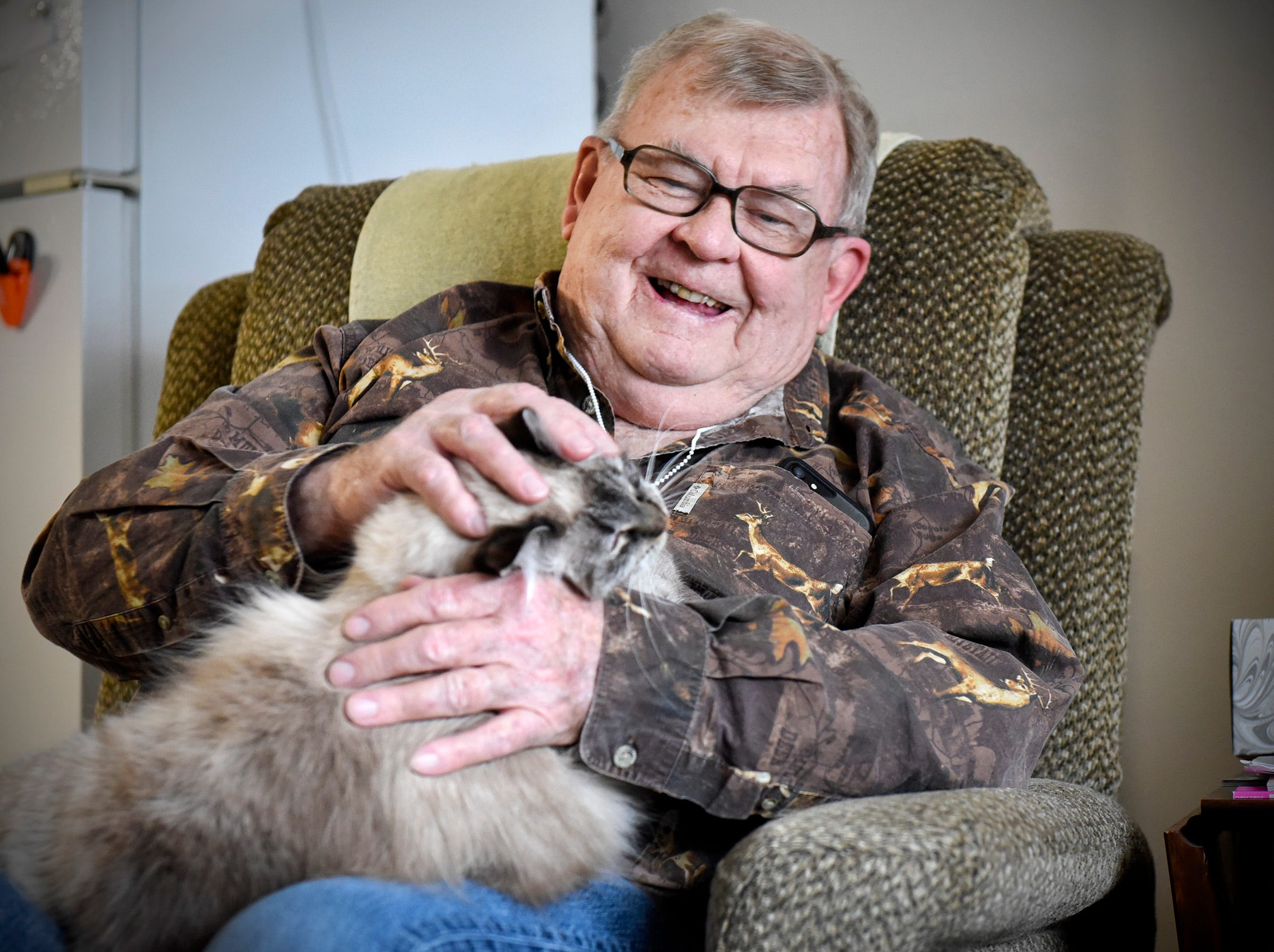 Harold Nelson plays with his cat Lena Wednesday, Dec. 5, at Ridgeview Place Senior Living in Sauk Rapids.