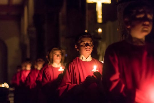 """Grant Schroers (Sartell) in candlelight procession at the start of """"A Ceremony of Carols"""" concert."""