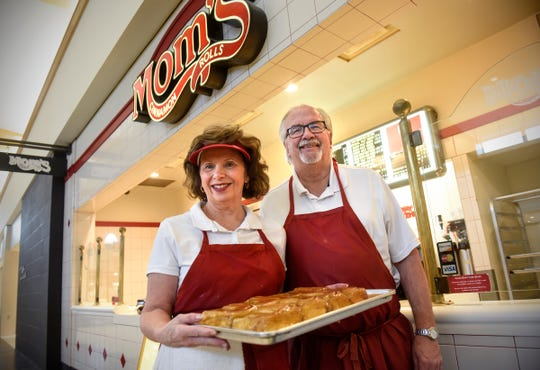 Chuck and Janet Wheeler hold a fresh tray of rolls Friday, Dec. 7, at Mom's Cinnamon Rolls at Crossroads Center in St. Cloud. The couple is retiring and closing the business at the end of the month after 30 years.