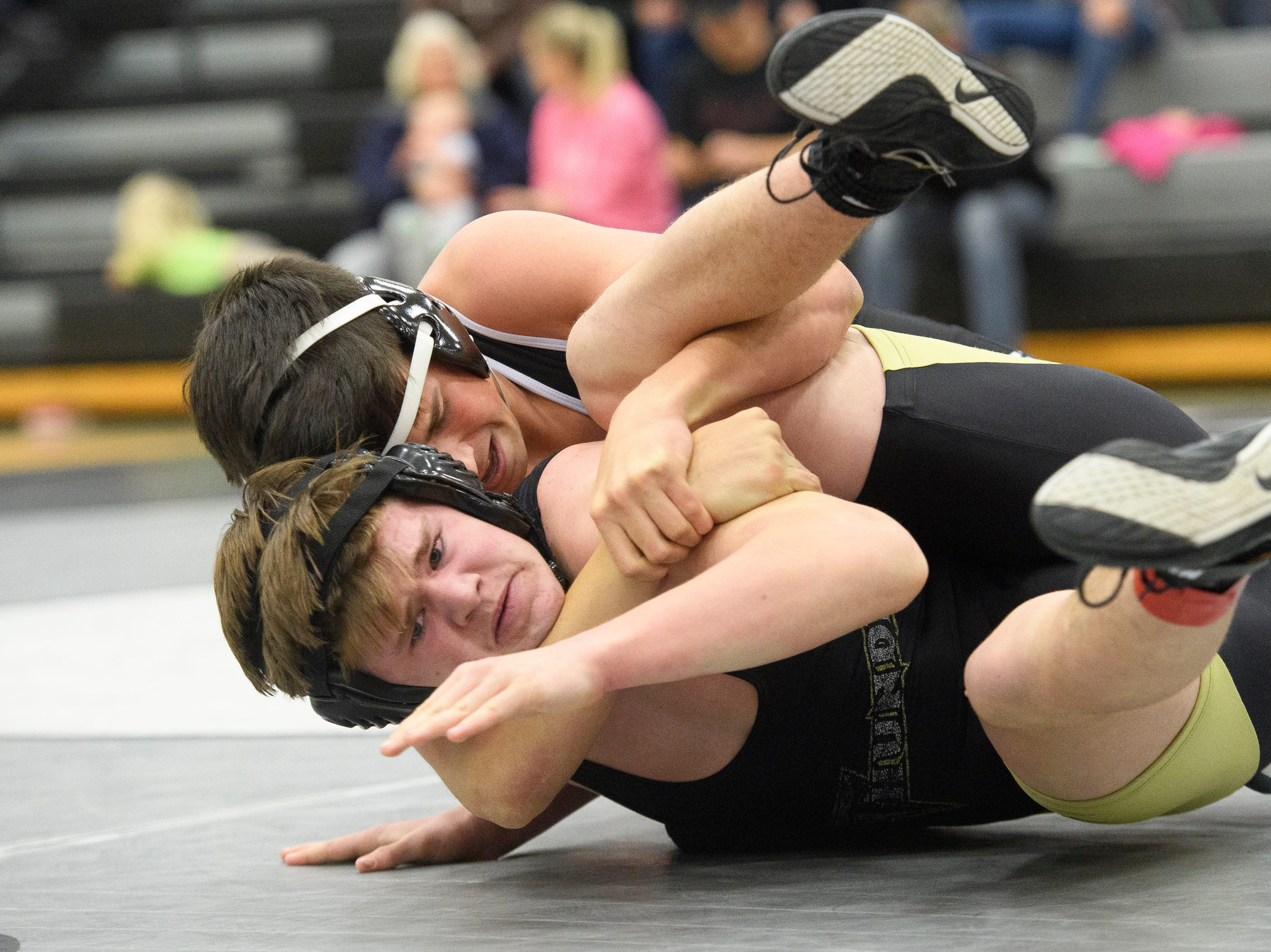 Desert Hills High School's Quade Jones looks for a way out of the grip of Canyon View's Dawson Stoor at CVHS Thursday, December 6, 2018. The Falcons won, 51-25.