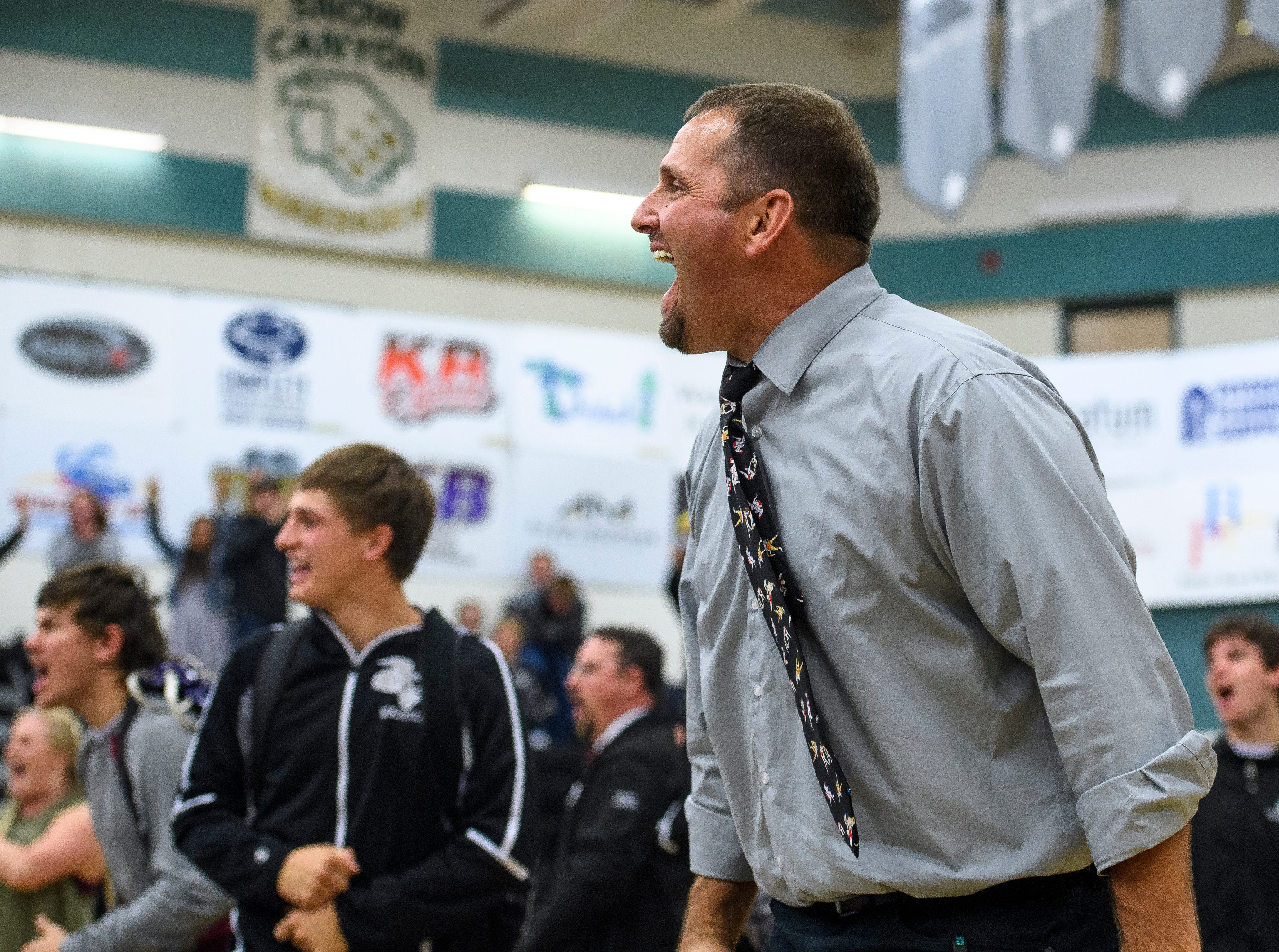 Canyon View wrestling head coach Dallas Lowry cheers as his team beats Desert Hills at CVHS Thursday, December 6, 2018. The Falcons won, 51-25.