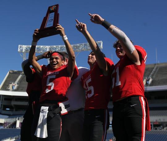 J.D. Jerry (15), Preston Reece (15), Jaxon Giles (51) celebrate with the trophy after NFC beat Champagnat Catholic 28-20 to win a Class 2A state championship on Friday, Dec. 7, 2018, at Orlando's Camping World Stadium.